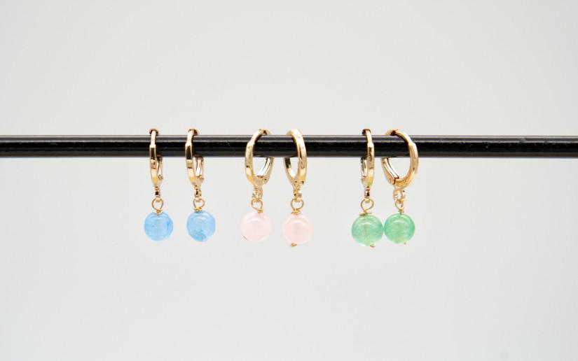 Kleine goldene Ohrringe mit hellblauen Stein